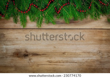 Pine tree border with red garland on old rustic wooden background - stock photo