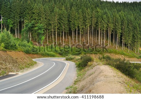 Pine trees and a winding road in a hilly Ardennes Landscape near Waimes in the Belgian East Cantons. - stock photo