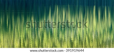 Pine trees reflecting in the gently rippling water of a high alpine lake. - stock photo