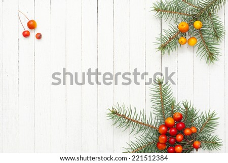 pine twig with forest berry on white wood  - stock photo