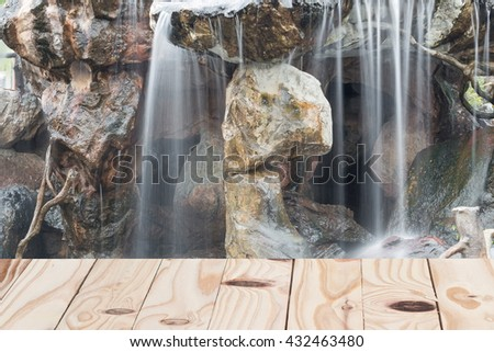Pine wooden floor and  nature Soft Waterfall  flowing over a stone in the garden.: space for add text above and may be used as background : - stock photo
