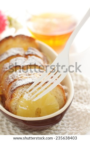Pineapple and bread pudding with English tea on background