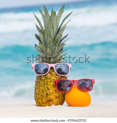 Pineapple and orange fruits in sunglasses on sand against turquoise caribbean sea water. Tropical summer vacation concept