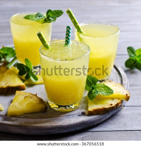Pineapple cocktail with pulp in a glass on a wooden background. Selective focus. - stock photo