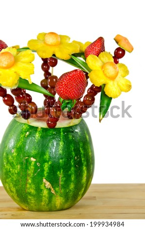 pineapple, grapes and strawberry bouquet in watermelon on a butcher block - stock photo