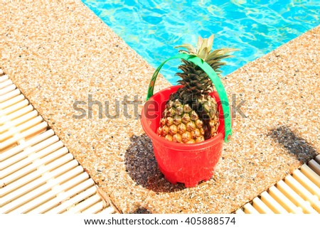 pineapple in toy bucket at swimming pool. - stock photo