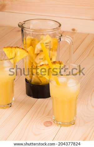 Pineapple Juice in two glasses on wooden background - stock photo