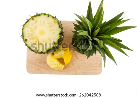 Pineapple on a wood chopping board isolated on white background. - stock photo