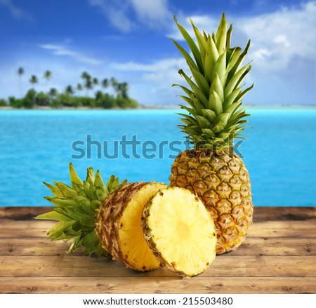 pineapple on wooden table in a tropical landscape - stock photo