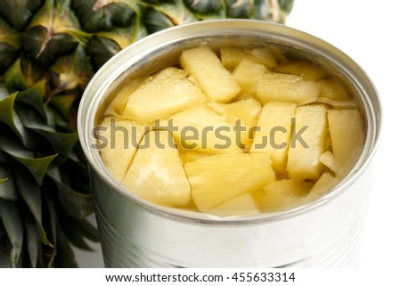 Pineapple pieces in tin on white next to pineapple.