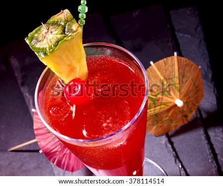 Pineapple red  cocktail with cherry and umbrella in highball glass . Top view. Food idea. - stock photo