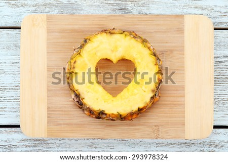 Pineapple slice with cut in shape of heart on wooden background - stock photo