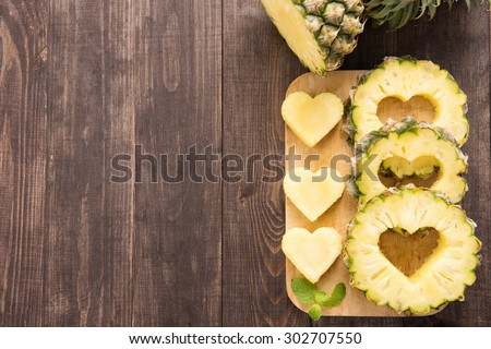Pineapple slices with a cut in the shape of hearts on wooden background. - stock photo