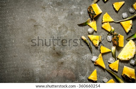 Pineapple slices with ice and leaves. On the stone table. Free space for text . Top view - stock photo