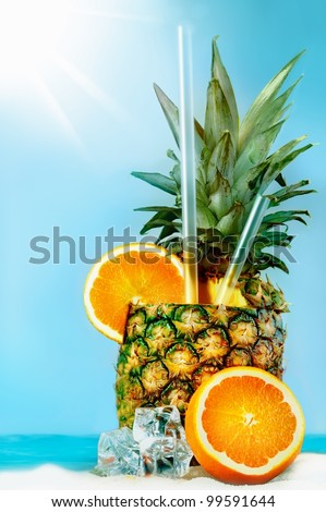 Pineapple with oranges and tubules on white beach sand. Fresh cold drink - stock photo