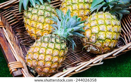 Pineapples in wicker basket at organic farmers market in Paris (France). - stock photo