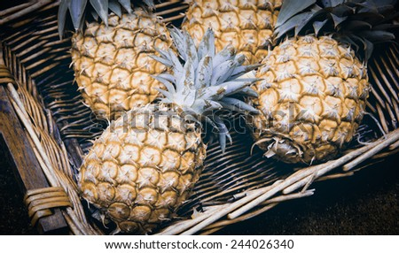 Pineapples in wicker basket at organic farmers market in Paris (France). Aged photo. - stock photo
