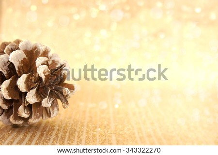 Pinecone on golden shiny background with copy space for text. Holiday background or greeting card. Selective focus - stock photo
