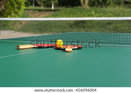 Ping pong ball with paddle on tennis table