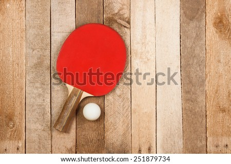 Ping pong paddle and ball on vintage wooden background - stock photo