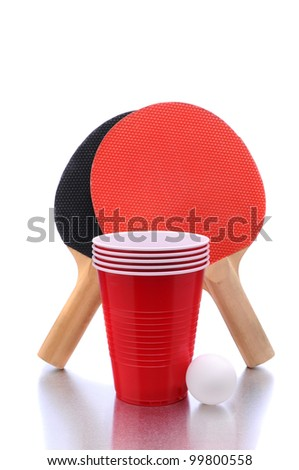 Ping Pong paddles and ball with cups for playing Beer Pong on a white background with reflection. - stock photo