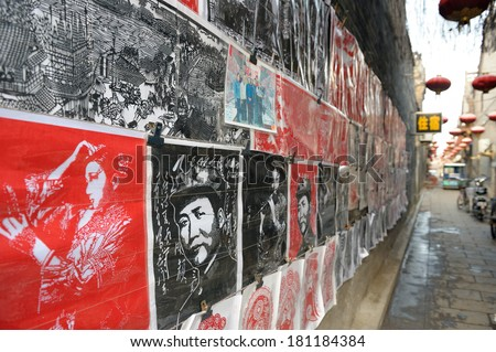 PINGYAO, CHINA - SEPTEMBER 10: Wall covered with Chinese posters, included old propaganda posters in narrow street on September 10, 2011 in Pingyao. - stock photo
