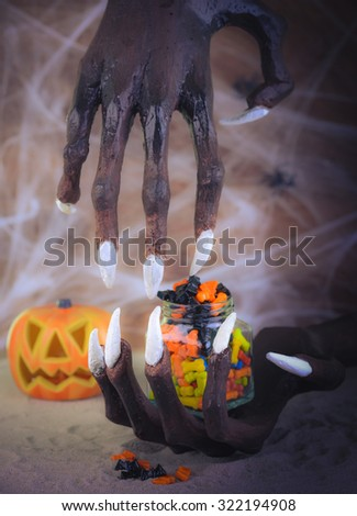 Pinhole effect Halloween witch hands and colorful candies - stock photo