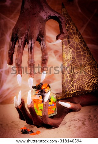 Pinhole effect of Halloween witch hands and colorful candies - stock photo