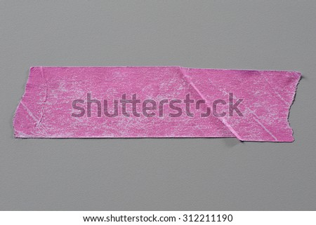 Pink Adhesive Tape on Grey Background with Real Shadow. Top View of  Masking Tape, Label or Paper Tag. Sticker Close Up with Copy Space for Text or Image - stock photo