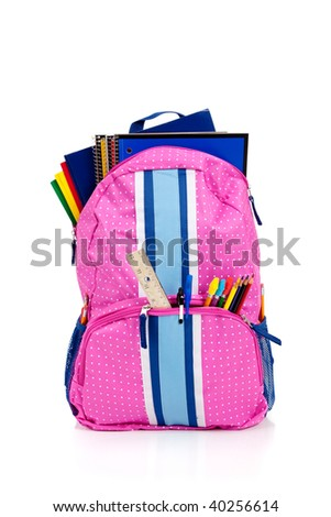 Pink and blue backpack with school supplies including notebooks, folders, ruler, pens, pencils - stock photo