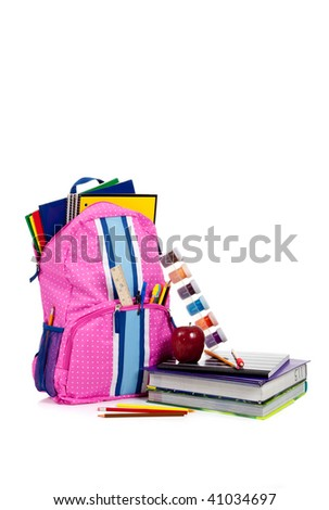 Pink and blue backpack with school supplies including notebooks, folders, ruler, pens, pencils, apple, paint and textbook on white with copy space - stock photo