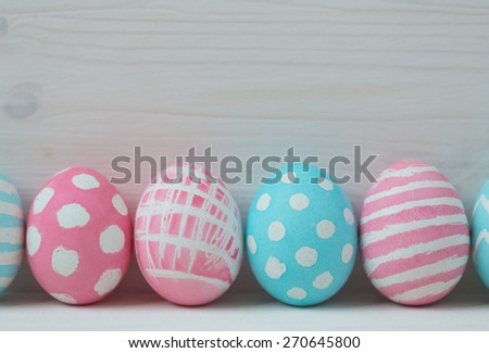 Pink and blue easter eggs on a wooden background - stock photo