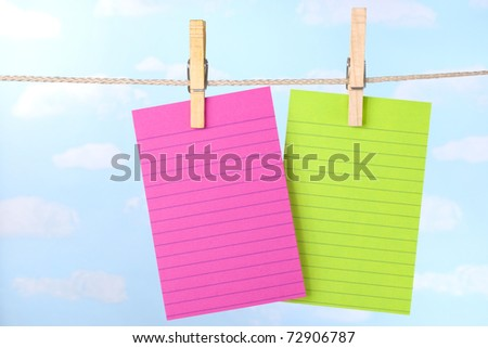 Pink and green paper note cards pinned to clothesline with a blue sky background