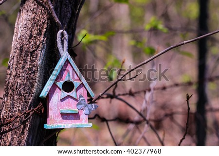 Pink and mint green birdhouse with butterfly hanging on old post with foliage and barbed wire fence blurred in background - stock photo