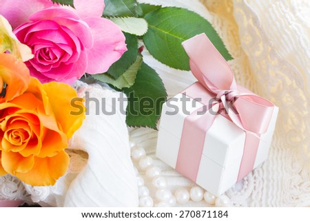 pink and orange roses with lace and gift box