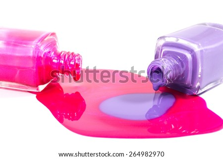 Pink and purple nail polish bottles with nail polish pouring from them on the white background - stock photo