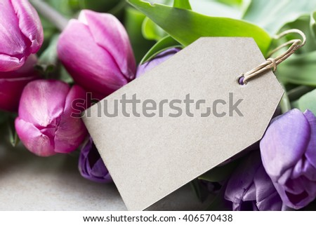 Pink and purple tulips and blank card with copy space for Mother's Day or Easter Greeting. - stock photo