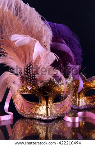 Pink and purple venetian mask on a black background mirror. - stock photo