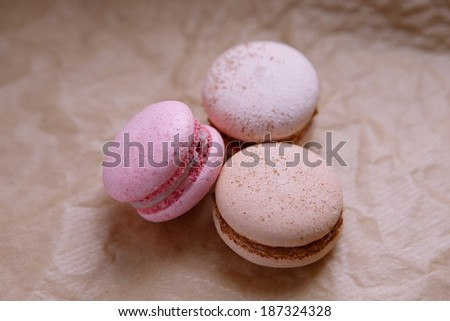 pink and two beige macaroons on craft paper with natural light