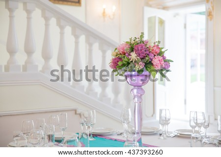 Pink and violet bouquet stands in a high vase on round dinner table