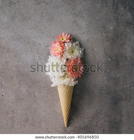 Pink and white flowers in ice cream cone on marble background. Minimal concept. Flat lay. - stock photo