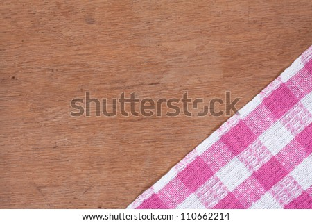 Pink and white kitchen textile texture on wood background - stock photo