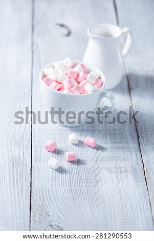 Pink and white marshmallows in a cup, over wood background.