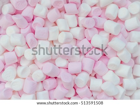 Pink and white mini marshmallows background, close-up texture. A pile of different mini puffy marshmallows. Marshmallow concept. Wallpaper for desktop. Top view.
