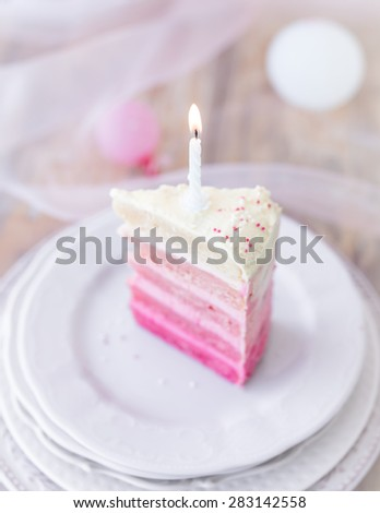 Pink and white piece of birthday cake with little burning candle. Selective focus. - stock photo