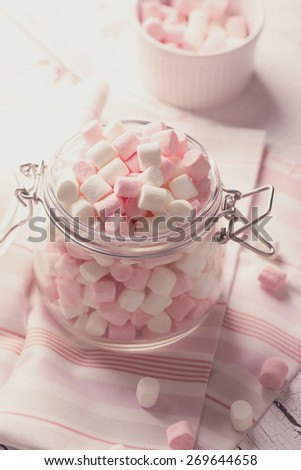 Pink and white small marshmallows in a glass pot on wooden table. Selective focus. Toned image - stock photo