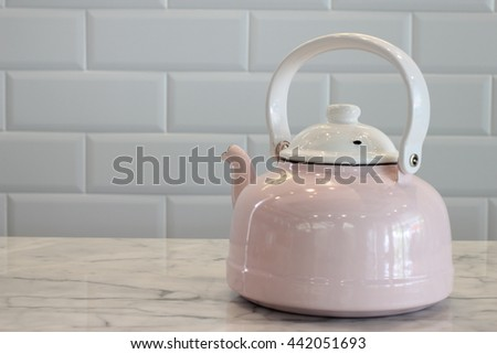 Pink and White Stovetop whistling kettle on table.