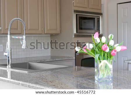 pink and white tulips in a modern grey kitchen - stock photo
