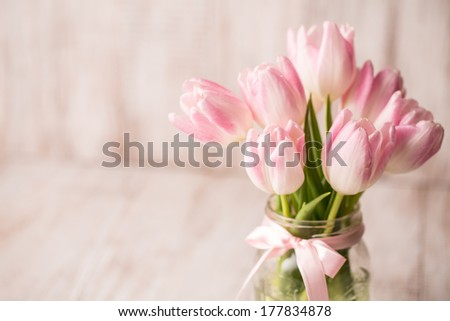 Pink and white Tulips in glass jar vase with pink bow