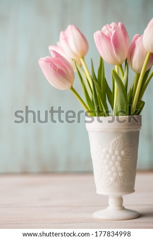 Pink and white tulips in white vase on blue background - stock photo